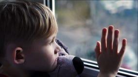 En härlig liten blond pojke som ut ser ett soligt fönster som väntar på hennes pappa för att komma hem från arbete stock video