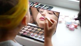 En härlig liten flicka på spegeln gör sig ett smink stock video