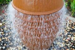 En härlig liten springbrunn i form av en brun vas, en tillbringare med fallande droppar av vatten på kulört stå för stenar arkivfoto