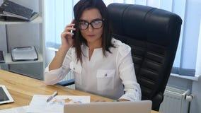 En härlig lyckad kvinna som talar på telefonen på det moderna kontoret stock video