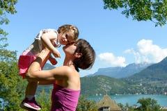 En härlig mamma är en kram till hennes dotter royaltyfria bilder