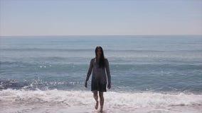 En härlig modell som barfota går ut ur havet med stora vågor som bryter på kusten långsam rörelse lager videofilmer