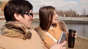 En härlig mogen moder och hennes vuxna dottersamtal, leende, går tillsammans på stadsgatan olika utvecklingar stock video