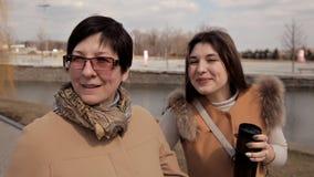En härlig mogen moder och hennes vuxna dottersamtal, leende, går tillsammans på stadsgatan olika utvecklingar arkivfilmer