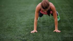 En härlig muskulös flicka i damasker och en väst gör en burpee på stadion Crossfit kondition, sund livsstil stock video