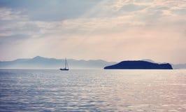 En härlig och dramatisk sikt av en yacht och en ö royaltyfri foto