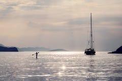 En härlig och dramatisk sikt av en yacht och en paddler arkivfoton