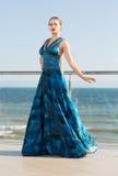 En härlig och elegant dam i en lång vinkande smaragdklänning poserar nära ett ljust blått hav Arkivbild