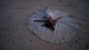 En härlig och lycklig brud ligger på sanden under solnedgången som fördelar en bröllopsklänning runt om henne Den original- idén  arkivfilmer