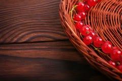 En härlig partisk sammansättning av en brun korg med den röda mogna vinbäret på en trätabell för mörk brunt Arkivfoto