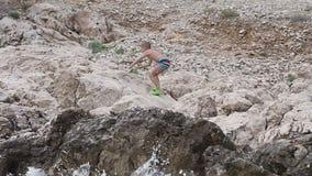 En härlig pojke som går på stranden av Adriatiskt havet och högt klättrar på vagga som kastar havsstenar i vattnet lager videofilmer