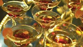 En härlig pyramid av exponeringsglas med champagne och stycken av frukt i den lager videofilmer