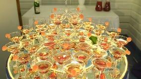 En härlig pyramid av exponeringsglas med champagne och stycken av frukt i den arkivfilmer