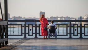 En härlig rödhårig flicka i en röd klänning och en grabb i en rullstol är på kanten av invallningen, att beundra fotografering för bildbyråer