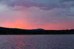 En härlig rosa solnedgång över en bergsjö Royaltyfri Bild