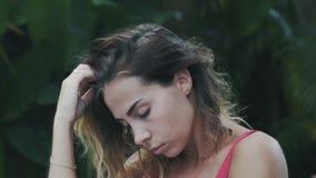 En härlig sexig modell med kort lockigt hår tycker om att koppla av i den tropiska djungeln som spelar med hennes hår, har en bru stock video