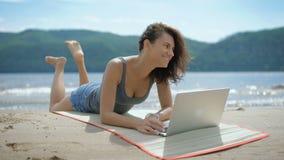 En härlig sexig ung le dam lägger på hennes tommy på en strand genom att använda bärbara datorn arkivfilmer