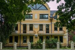 En härlig sikt av fasaden av byggnaden med balkonger som står bak ett lågt staket med att växa gröna buskar Fotografering för Bildbyråer