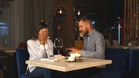 En härlig skäggig man ger en gåva till hans flickvän i en restaurang stock video