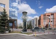 En härlig skulptur av en klocka med tecken av konstellationer, mot en bakgrund av ett stadslandskap Arkivbild