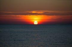 En härlig solinställning på horisonten på havet royaltyfri foto