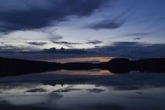 En härlig solnedgång över en skogsjö med moln reflekterade i vattnet royaltyfri fotografi