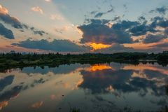 En härlig sommarafton Den dramatiska solnedgången reflekterar i vattnet av en flod eller en sjö på utkant för en stad Fotografering för Bildbyråer