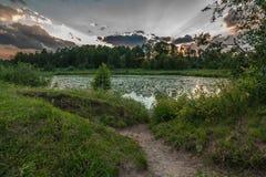 En härlig sommarafton Den dramatiska solnedgången reflekterar i vattnet av en flod eller en sjö på utkant för en stad Royaltyfria Foton