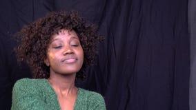 En härlig svart kvinna med lockigt hår dansar långsamt i studion, ultrarapid stock video