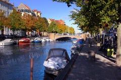 En härlig träd-fodrad kanal med fartyg och hus arkivfoto
