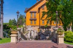 En härlig trappuppgång med moment med härlig arkitektur som leder till huset med stora bunkar med nya blommor Arkivbild