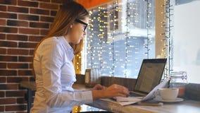 En härlig ung affärskvinna arbetar i ett kafé och undertecknar avtal