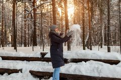 En härlig ung blond flicka i ställningar för en vinterbarrskog i en grå hatt och handskar och ett mörkt - blått omslag som spelar royaltyfria foton