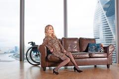 En härlig ung blond flicka i en trendig klänning med ett handikapp som poserar på en lädersoffa mot bakgrunden royaltyfri fotografi