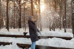 En härlig ung blond flicka i en vinterbarrskog är stå och fånga med hennes händer snön som faller från royaltyfri foto