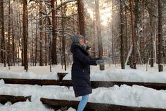 En härlig ung blond flicka i en vinterbarrskog är stå och fånga med hennes händer snön som faller från royaltyfria foton