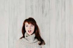 En härlig ung brunettkvinna i en grå sweater, förvånade stora ögon, öppnar munnen, med ljus bakgrund emotionell kvinnlig arkivfoton