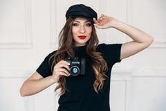 En härlig ung flicka, har en ren sund framsida, långt silkeslent hår, ett ljust smink, är iklädd ett svart lock och t royaltyfri foto