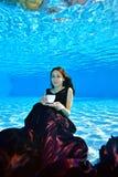 En härlig ung flicka i en Bourgogneklänning sitter och poserar undervattens- längst ner av pölen, rymmer en vit kopp i hennes han royaltyfri fotografi
