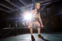 En härlig ung flicka i idrottshallen utbildar musklerna av benen, och baksida, deaet övar deadlift, sitter med vikt, hållstång I Arkivfoton
