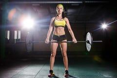En härlig ung flicka i idrottshallen utbildar musklerna av benen, och baksida, deaet övar deadlift, sitter med vikt, hållstång I Royaltyfri Foto