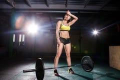 En härlig ung flicka i idrottshallen utbildar musklerna av benen, och baksida, deaet övar deadlift, sitter med vikt, hållstång I Fotografering för Bildbyråer
