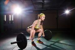 En härlig ung flicka i idrottshallen utbildar musklerna av benen, och baksida, deaet övar deadlift, sitter med vikt, hållstång I Arkivbild