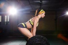 En härlig ung flicka i idrottshallen utbildar musklerna av benen, och baksida, deaet övar deadlift, sitter med vikt, hållstång I Arkivbilder