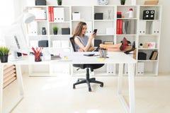 En härlig ung flicka i kontoret har satt hennes fot på tabellen och rymmer exponeringsglas och en telefon Royaltyfria Foton