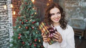 En härlig ung flicka i en tröja och strumpor som sitter nära härliga julgranar och in håller, räcker gåvor arkivfilmer