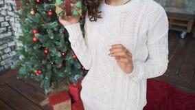En härlig ung flicka i en tröja och strumpor som sitter nära härliga julgranar och in håller, räcker gåvor stock video
