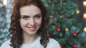 En härlig ung flicka i en tröja och strumpor som sitter nära härliga julgranar och in håller, räcker gåvor lager videofilmer
