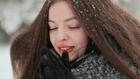 En härlig ung flicka med chic långt hår tycker om fallande insnöad vinter tätt med textsidan upp lager videofilmer