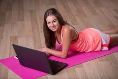 En härlig ung flicka med en svart bärbar dator som ligger på en träbakgrund En sportive flicka i en färgrik sportswear kopia Fotografering för Bildbyråer